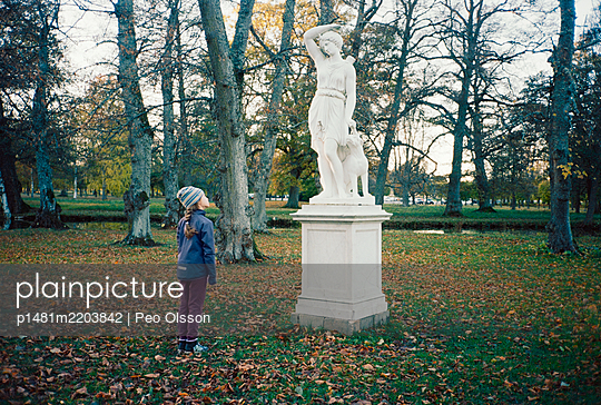 Girl stands in front of sculpture in a park - p1481m2203842 by Peo Olsson