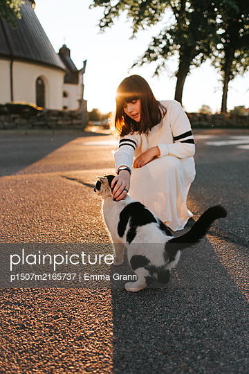Petting my cat in the sunset - p1507m2165737 by Emma Grann