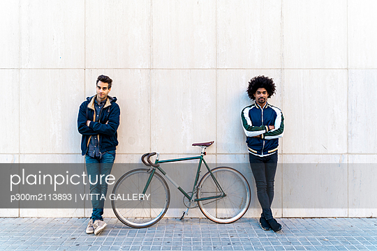 Portrait of two casual men with bicycle standing at a wall - p300m2113893 von VITTA GALLERY
