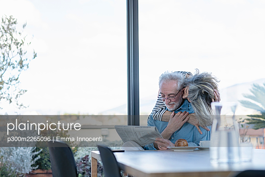 Senior woman romancing with man while standing by window at home - p300m2265096 by Emma Innocenti