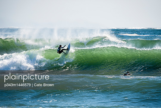 Men surfing large wave