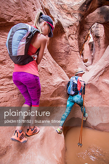 Two women exploring Peak-a-boo slot canyon, Grand Staircase-Escalante National Monument, Utah, USA - p343m1578152 by Suzanne Stroeer