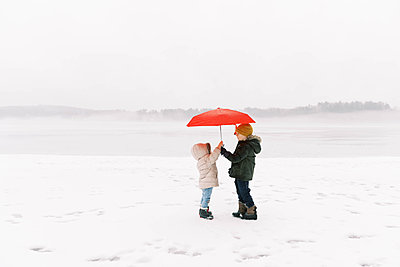 A brother and sister having fun in the wintery rain. - p1166m2157465 by Cavan Images