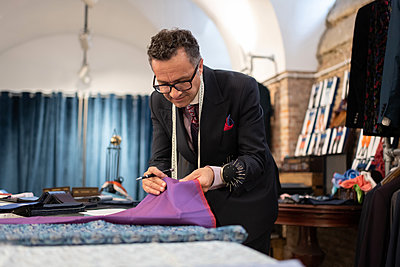 Mature tailor choosing fabric on table - p1166m2261411 by Cavan Images