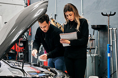 Two mechanics help each other in the work of a garage - p1166m2268344 by Cavan Images