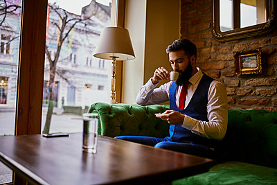 Fashionable young man sitting on couch in a cafe drinking coffee and using cell phone - p300m1549695 by Zeljko Dangubic
