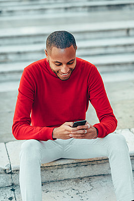Smilig young man wearing red pullover sitting on stairs using cell phone - p300m2070493 von Javier Sánchez Mingorance