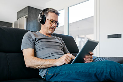 Mature man wearing headphones while using digital tablet in living room - p300m2266602 by Josep Rovirosa
