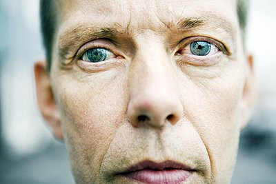Close-up of a mature man wearing artificial green eyes - p3483547 by GUSK