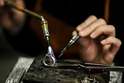 Close-up of jeweler heating ring with welding torch at workshop - p426m2097343 by Katja Kircher