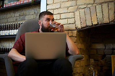 Young man using laptop drinking tumbler of spirit in public house - p429m1418088 by Peter Muller