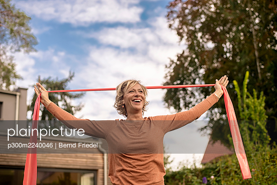 Smiling woman holding exercise band while standing at back yard - p300m2240046 by Bernd Friedel