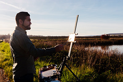 Side view of painter painting on canvas at field against sky - p1166m1473622 by Cavan Images