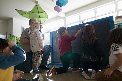 Preschool students at blackboard in classroom - p1192m1560211 by Hero Images