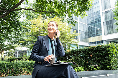Smiling businesswoman using mobile phone while sitting at office park - p300m2227070 by Pete Muller