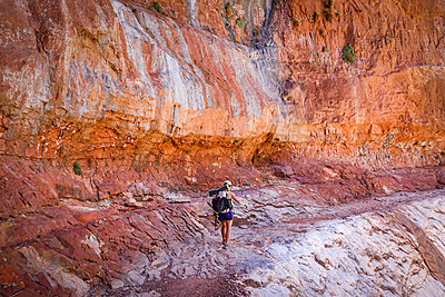 Young woman hiker traversing massive sandstone features of Grand Canyons North Rim, Grand Canyon, Arizona, USA - p343m2032475 by Suzanne Stroeer