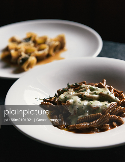 Freshly made pastas and herbs on a moody restaurant table - p1166m2191921 by Cavan Images