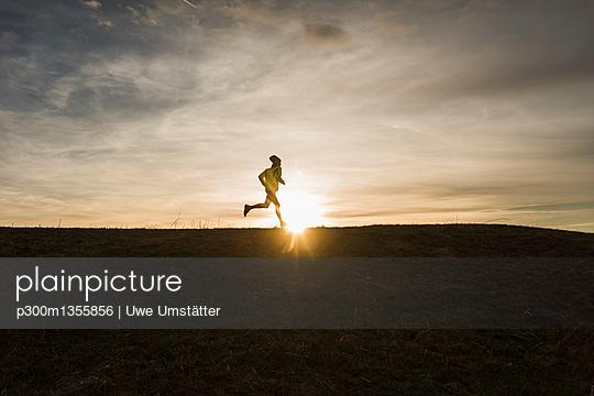 Man running in rural landscape at sunset - p300m1355856 by Uwe Umstätter