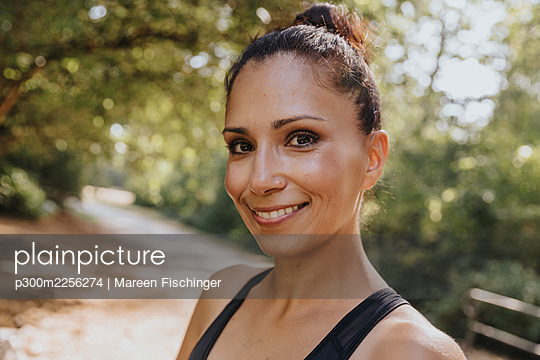 Sportswoman smiling while standing at park - p300m2256274 by Mareen Fischinger