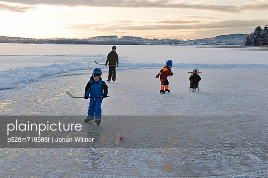 Children playing ice hockey on frozen lake