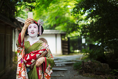 A woman dressed in the traditional geisha style, wearing a kimono and obi, with an elaborate hairstyle and floral hair clips, with white face makeup with bright red lips and dark eyes taking a selfie. - p1100m1185722 by Mint Images