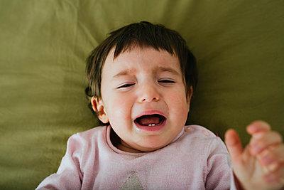 Portrait of crying baby girl lying on bed - p300m1562742 by Gemma Ferrando