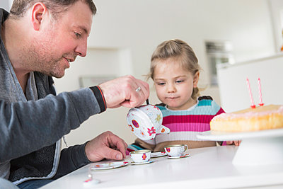 Father and daughter playing with doll's china set - p300m2189098 by Floco Images