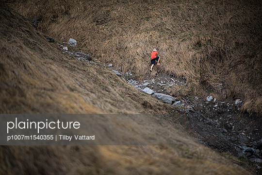 Man climbing in the grass in the mountain - p1007m1540355 by Tilby Vattard