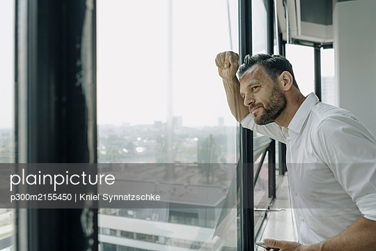 Mature businessman looking out of window in office - p300m2155450 by Kniel Synnatzschke