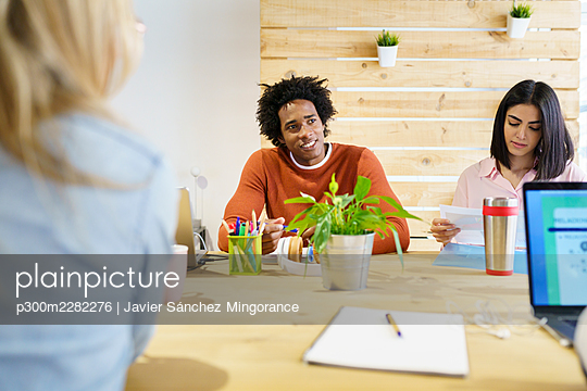 Multi-ethnic coworkers at conference table in board room - p300m2282276 by Javier Sánchez Mingorance