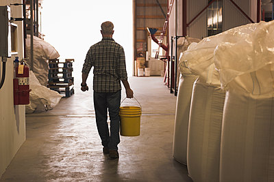 Rear view of man carrying with bucket full of grains in factory - p1315m1565229 by Wavebreak