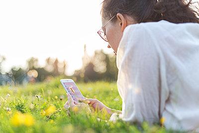 Junge Frau mit Smartphone im Park - p1396m1481202 von Hartmann + Beese