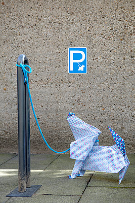 Origami dog in front of concrete wall, parking sign - p300m2012947 von Petra Stockhausen