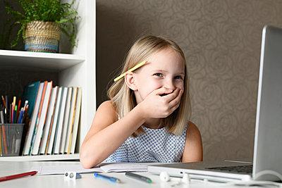 Laughing girl sitting at table at home using laptop - p300m2155994 by Ekaterina Yakunina