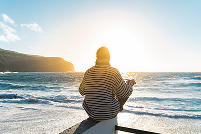 Man meditating at the coast at sunset, Sao Miguel Island, Azores, Portugal - p300m2169852 by VITTA GALLERY