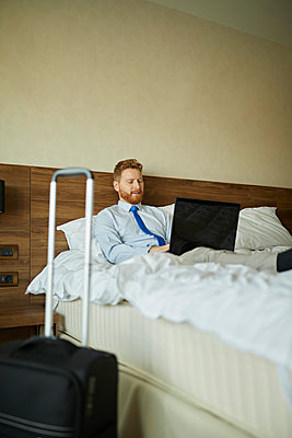 Businessman lying on bed in hotel room using laptop - p300m2170967 by Zeljko Dangubic