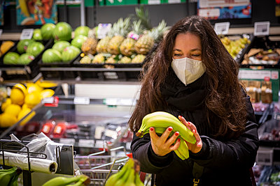 Mature woman buying bananas while grocery shopping during COVID-19 - p300m2243911 by Nadine Ginzel
