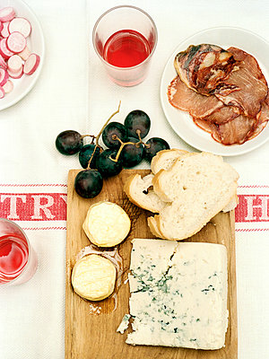 Blue cheese and sliced bread with grapes and salami on tabletop, Spain - p349m2167741 by Polly Wreford