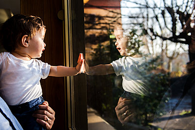 Baby boy in father's arms looking through and touching window - p429m1226855 by Bonfanti Diego