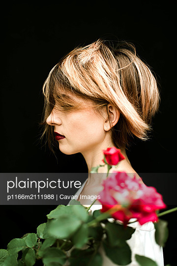Portrait of attractive woman with roses  against black background - p1166m2111988 by Cavan Images