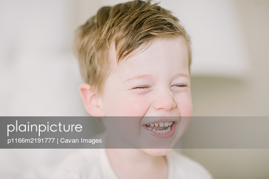 Closup of toddler boy laughing with eyes closed - p1166m2191777 by Cavan Images