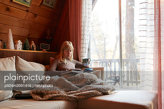 Woman reading book on sofa at home - p924m2091416 by heshphoto