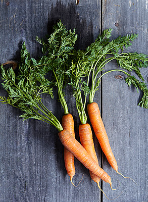 Overhead view of carrots on wooden table - p1166m1534683 by Cavan Images