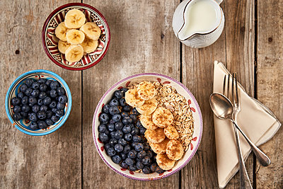 Homemade oatmeal granola with  blueberry and banana in wooden bowl, su - p1166m2111744 by Cavan Images
