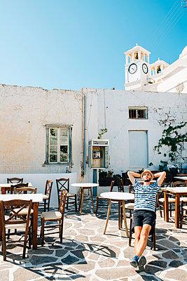 Greece, Milos, Klima, Man sitting in empty cafe, relaxing - p300m1206126 by Gemma Ferrando