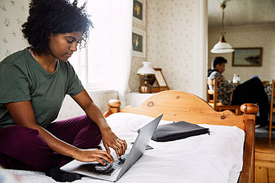 Young woman using laptop on bed while friend sitting in background at home - p426m2117175 by Maskot
