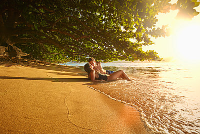 Couple laying on beach in waves and kissing - p555m1301920 by Colin Anderson