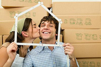 Junges Paar vor vielen Umzugskartons sieht durch Meterstab als Haus - p6090367f von DRESDEN photography