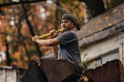 Mid adult man chopping logs in autumn forest, Upstate New York, USA - p924m1404227 by heshphoto