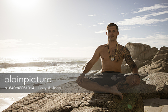 Man practises meditation on the beach in the sunshine - p1640m2261014 by Holly & John